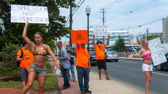 Ocean City street performers hold signs to attract signatures during a protest of new street performer regulations outside of Ocean City Town Hall.