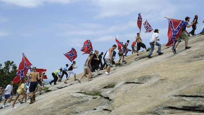 Confederate flag supporters climb Stone Mountain to protest of what they believe is an attack on their Southern heritage during a rally at Stone Mountain Park in Stone Mountain, Ga., on Saturday.