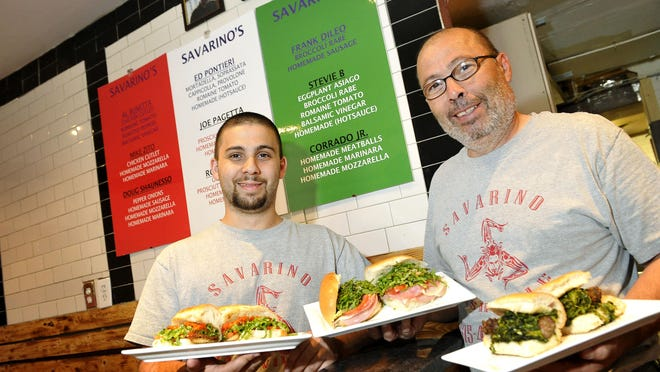 Carmelo and Corrado Savarino show off sandwiches named for former beloved customers who have died.