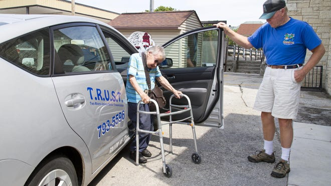 "Two Rivers Senior Center T.R.U.S.T. car volunteer driver Gib St. Pierre, 69, right, helps Helen Lachowicz, 85, to get out of the car at the senior center on Tuesday, Aug. 18, in Two Rivers. ""It's nice for people. They really like it,"" St. Pierre said."