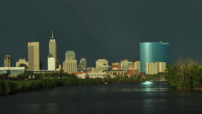 The sun reflects off the Downtown Indianapolis skyline looking down the White River from New York Street.