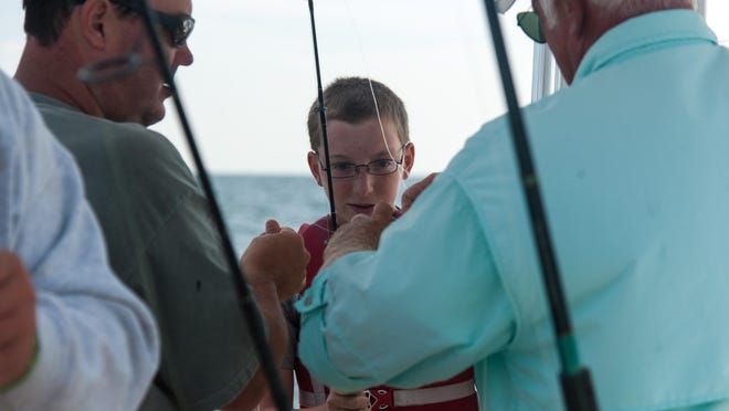 Micheal Erb, 13, eyes his catch during a fishing trip off the coast of Bethany Beach.