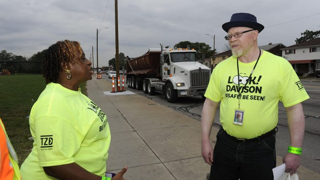 Rita Screws, left, and Brian Finch stand on Davison between I-96 and M-10 to get the word out to be safe in Detroit on Friday.