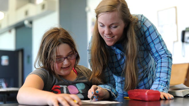 Karlee Snyder, a third-grader at Unioto Elementary School gets help with her homework from YMCA School Age Counselor Nena Park during the after school program Thursday at the YMCA of Ross County.