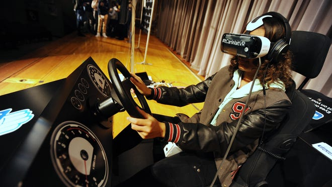 """University High School Academy senior Karley Foster, 17, gets behind the wheel of the AT&T VR driving simulator during the """"It Can Wait"""" Road Tour stop at University High School Academy in Southfield on Nov. 18, 2015. While looking through the Google Glass googles, students witnessed the perils of distracted driving up-close."""