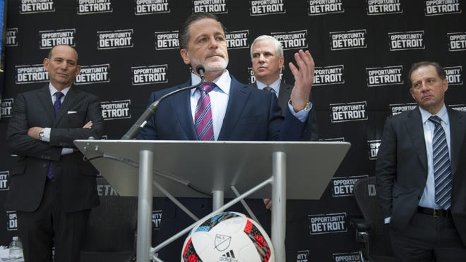 Rock Ventures owner Dan Gilbert flanked by Major League Soccer's Commissioner Don Garber, left, and Rock Ventures representative Matt Cullen presents his vision for a soccer stadium at the stalled Wayne County Jail site on Wednesday.
