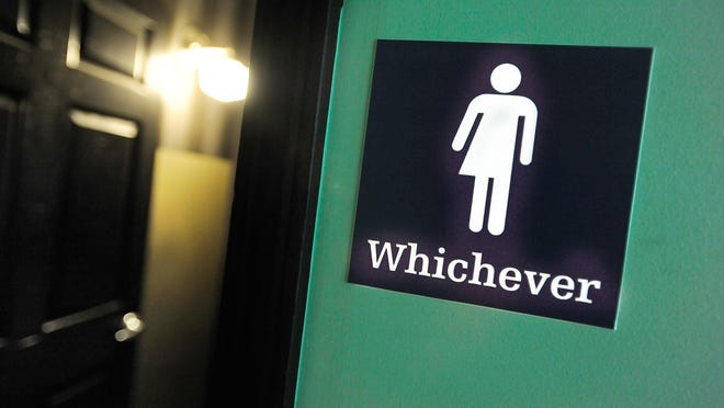 A gender neutral sign is posted outside a bathrooms at Oval Park Grill in Durham, North Carolina. Debate over transgender bathroom access has spreads nationwide.