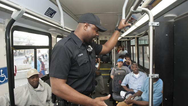 Detroit transit police officer Dujuan Brown talks to a disruptive passenger to determine if he should be removed from a bus and given a free ticket for the next bus.