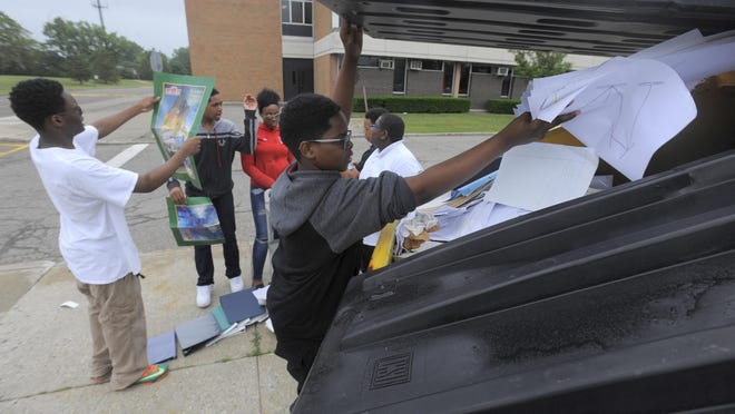 Joshua Evans, 15, tosses paper into a recycle bin Thursday outside Southfield-Lathrup High. The 49-year-old school is closing for good, a victim of falling enrollment and worsening district finances.