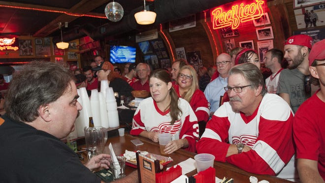 Tommy Burelle, left, owner of Tommy's Detroit Bar and Grill, plans to shuttle patrons to the Red Wings' new home next year. Other bars around Joe Louis Arena plan to do the same.
