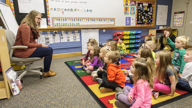 Christina O'Lear leans in to offer instruction to her class at Altoona Elementary's preschool program.