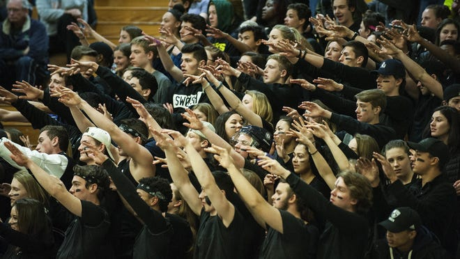 Burlington fans hold up their hands during a free throw during the boys semifinal basketball game between the Burlington Seahorses and the Rutland Raiders at Patrick Gym on Tuesday night.