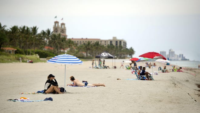 Sunbathers at Midtown Beach enjoy warm weather on Monday after restrictions limiting public beaches in Palm Beach to active use only were rescinded. Public beaches within the Town of Palm Beach are now open without emergency restrictions.