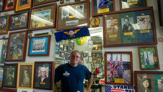 Village Barbershop owner Bobby Paige, seen in 2014 surrounded by photos of veterans, is among small businesses forced to close again after closing for more than two months due to the coronavirus pandemic.