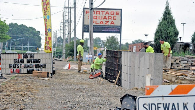 Construction crews continued work on the new bike path along Portage Road in front of the Portage Square Plaza in Wooster on Thursday.