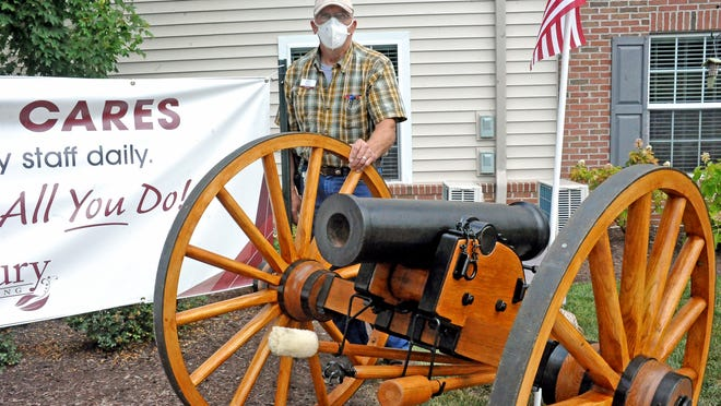 Bill Roeder, a maintenance worker at Danbury Senior Living in Wooster, stands with this scaled down model of an 1841 Civil War cannon that he built.