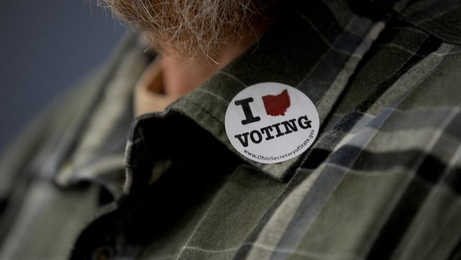 A voter displays his vote sticker after voting at at The Chapel in Marlboro, Tuesday, November 6,  2018.