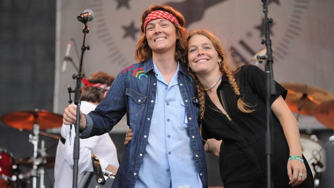 Brandi Carlile, left, and Maggie Rogers embrace before a performance at the 2018 Newport Folk Festival.
