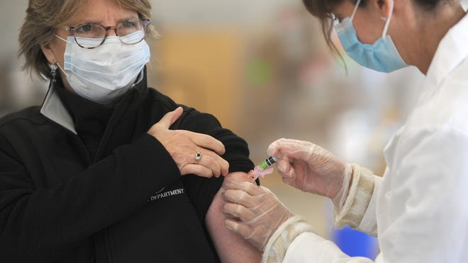 Betsy Sorensen, a principal clerk with the Orleans Health Department, left, receives a flu shot from pharmacist Maria Michaud. Sorensen was helping out with Wednesday's clinic, which was run by Cape Cod Healthcare. To see more photos, go to www.capecodtimes.com/photos.