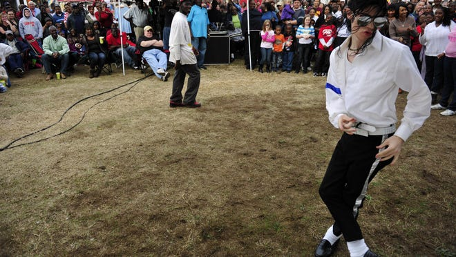 Michael Jackson impersonator Joey Fuignum (right)of Aiken, South Carolina participates in a spur of the moment dance-off with Chitlin Strut winner Neil Evans (center) during the Chitlin Celebration in Salley, South Carolina on Saturday, November 26, 2011.