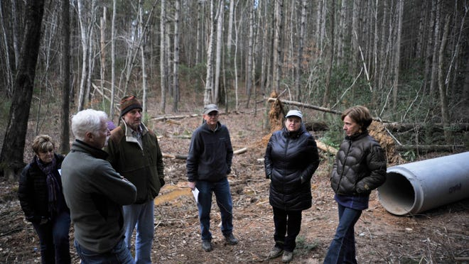 Opponents of a state shooting range gathered at its proposed site near Lake James, including Sue Crotts, second from right, chair of the local chapter's Blue Ridge Environmental Defense League. Road improvements have begun in the area.