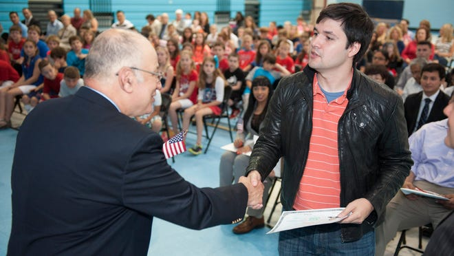 Marlton Elementary School Principal Julio Feldman gives a certificate of U.S. citizenship to Venezuelan immigrant Hugo Jimenez, 24, of Marlton, during a naturalization ceremony at Marlton Elementary School. Monday, June 9, 2014.