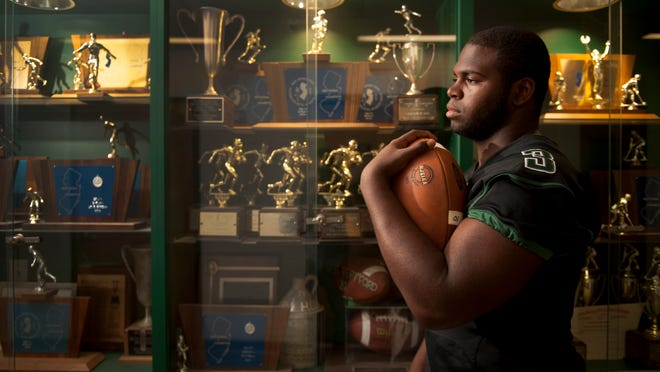 Top and above photos: West Deptford football player Gerald Owens stands by the  high school's trophy case.