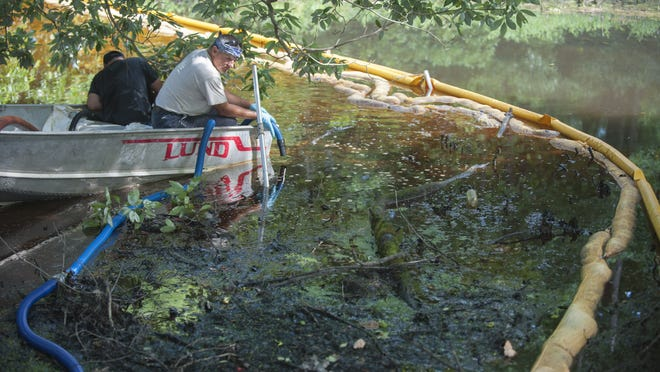 Workers clean oil out of Spring Lake in Washington Township on Monday after an oil spill on Sunday contaminated the lake.