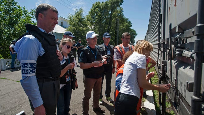 Deputy head of the OSCE mission to Ukraine Alexander Hug, left, watches as the train car is locked, on the platform as a refrigerated train loaded with bodies of the passengers prepares to depart the station in Torez, eastern Ukraine, 15 kilometers (9 miles) from the crash site of Malaysia Airlines Flight 17, Monday, July 21, 2014. Another 21 bodies have been found in the sprawling fields of east Ukraine where Malaysia Airlines Flight 17 was downed last week, killing all 298 people aboard. International indignation over the incident has grown as investigators still only have limited access to the crash site and it remains unclear when and where the victims' bodies will be transported. (AP Photo/Evgeniy Maloletka)