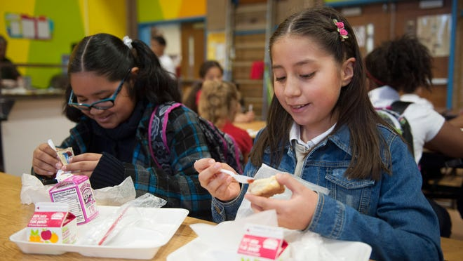 Fourth-graders Lesli Hernandez and Donaji  Mendieta eat  before  class Tuesday at Sharp Elementary School, Camden. Sharp is among  schools now ensuring students are offered breakfast even if they arrive late. JOHN ZIOMEK/COURIER-POST Sharp Elementary School 4th graders Lesli Hernandez and Donaji Meneieta eat breakfastprior to the start of school. Sharp is among Camden City schools participating in a program that brings breakfast directly into the classroom during first period. Tuesday, April 15, 2014.