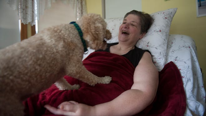 After being diagnosed with ALS nearly two year ago, Palmyra resident Carol Resides has outlived most doctor's expectations. Despite losing every bodily function beside sight and speech to ALS, the 56-year-old ALS advocate is glad to have witnessed the groundswell of support for ALS Ice Bucket Challenge. Here she shares a moment with her dog Doodles. Thursday, September 11, 2014.