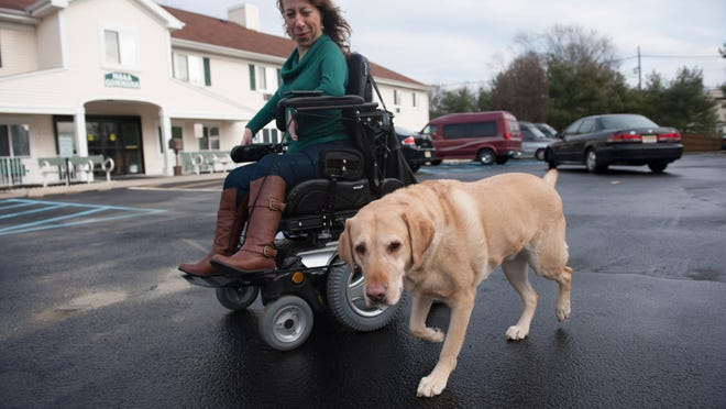 Top, Cherry Hill resident Erica Barker, 38, holds a paintbrush in her mouth to paint. Above, Barker  takes her service dog, Cyrus, for a walk around her building.  Photos by JOHN ZIOMEK/COURIER-POST Cherry Hill resident Erica Barker, 38, was born with Arthrogryposis multiplex congenita, a birth defect characterized by multiple underdeveloped joints, muscles, tendons, ligaments, and skin restricting normal movement at birth. Here she takes her service dog Cyrus for a walk around her building.