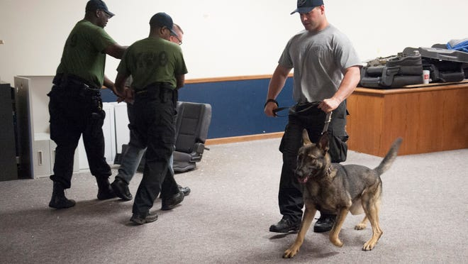 Camden County police officer Joe Cella walks with Moose during a K-9 training program last week at the former Voorhees Municipal Building.