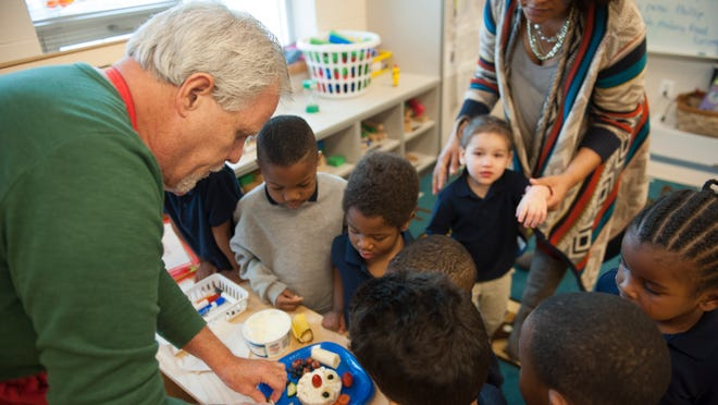 Paul Carden, 60, of Maple Shade, leads a cooking demonstration for Pre-K students at the Early Childhood Development Center in Camden. Carden showed the kids how to spread cream cheese on a rice cake and added fruits and vegetables to make a face. Tuesday, December 16, 2014.