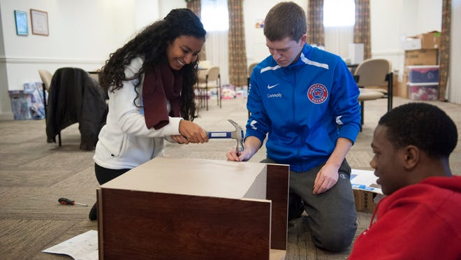 Washington Twp. High School students Alexa Mangual, Will Connolly and Norris King put together furniture at the Ronald McDonald House in Camden. Monday, January 19, 2015.