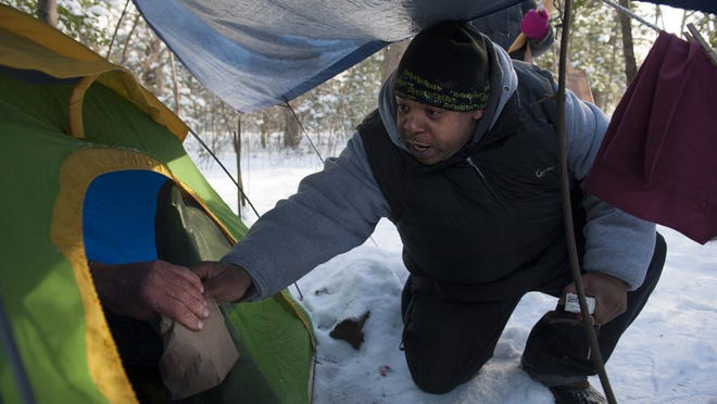 File: McNeil Byers with Collaborative Support Program NJ, an outreach organization, gives a bag lunch to Robert, a 69-year-old homeless Navy veteran, at his campsite in a wooded area in Berlin on January 29, 2014. Volunteers are counting the homeless in seven New Jersey counties.