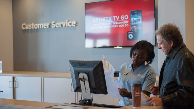 Comcast customer service rep Nyshaya Carrington assists Jeff Marcus of Mount Laurel Wednesday at the Xfinity store in Mount Laurel.