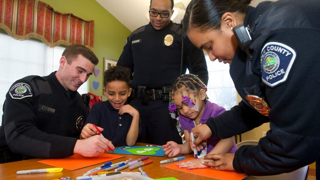 2/10/15 -- (L to R) Camden County Metro Officers Daniel Radetich, Stephen Walters and Brenda Santiago make valentines with Daquan Langston, 8, and Tamara Williams, 5, both of Camden as part of a community policing event held at the Chelton Terrace Community Center in Camden Tuesday afternoon. PHOTO/AVI STEINHARDT