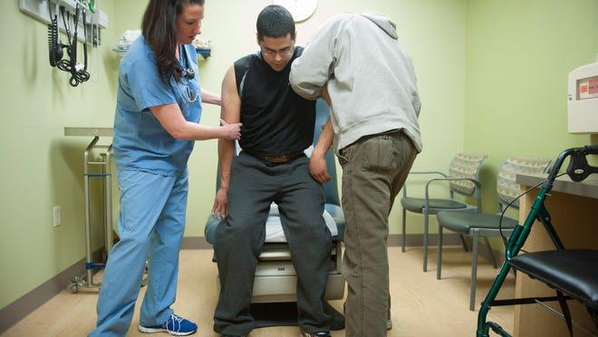 Nurse Practitioner Bridget Hopkins and Hainesport resident Al Melendez help Al's son Andrew Melendez, sit as Hopkins examines his back pain at Virtua Urgent Care in Mt. Laurel. Monday, March 9, 2015.