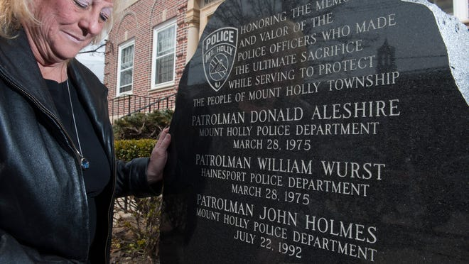 Cheryl Wurst, the close cousin of slain Hainesport police officer Bill Wurst, looks at the memorial stone outside township municipal building. Two Mount Holly police officers and Wurst were shot by sniper James Carhart on March 28, 1975, from the window of a Garden Street duplex, now an apartment. Wednesday, March 25, 2015.
