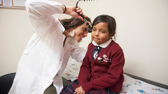 Katie Capano, nurse-practitioner with Rutgers/LEAP Health and Wellness Center, a new in-school health center staffed with nurse-practitioners and serving students and families of LEAP Academy in Camden, examines the ears of first-grader Jenaya Santiago.