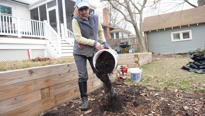 Audubon farmer Julie Pierre works the soil at a client's home in Collingswood. Pierre sells shares of her produce and makes deals with residents to use a portion of their yard to grow produce in exchange for a portion of the produce.