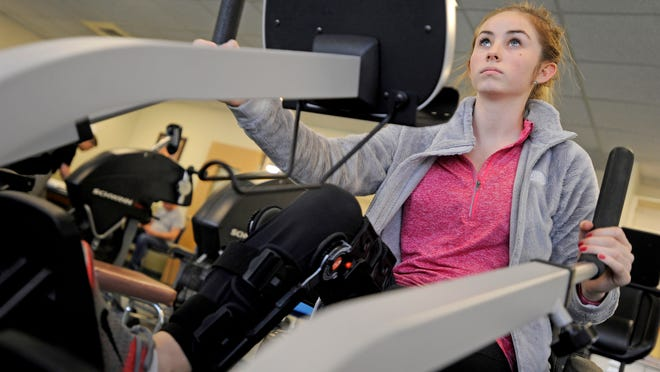 Payton Reuter, 17, an 11th-grader at Piketon High School wears her leg brace as she warms up before beginning physical therapy at Adena Rehabilitation and Wellness Center on Wednesday. Reuter tore her ACL for a second time but is planning to be ready to play volleyball next season.
