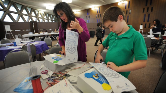 Judy Allen of Novi and her son, Benjamin, 9, add calendars to Rosh Hashana care boxes that include honey, challah and applesauce. Volunteers decorated each box to be delivered to Jewish senior citizens.
