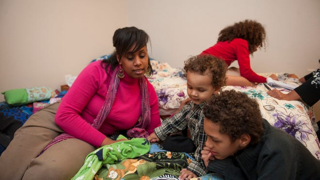 Angela Boyce and three of her five children, Adrielle, 8; Israel, 2, and Gabriel, 10, play in their Woodhaven home. Boyce, who was homeless for a time, has been given help from the Wayne Metropolitan Community Action Agency who got the family into their current apartment.