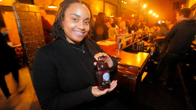 Nailah Ellis-Brown holds a bottle of Ellis Island Iced T <137>, Thursday Feb. 19, 2015, <137>during the MichiganFunders.com launch party <137>for MichiganÕs First Equity Crowdfunding Platform <137>at Detroit City Distillery, Detroit.<252><137>Marke in Eastern t. (Steve Perez / The Detroit News)<252><137>