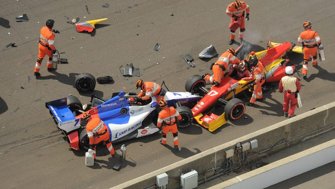 Safety crew attend to Mikhail Aleshin and pole  sitter, Sebastian Saavedra  crash at the start of the race,  Saturday May 10,  2014 at The Indianapolis Motor Speedway, during  the Grand Prix of Indianapolis.