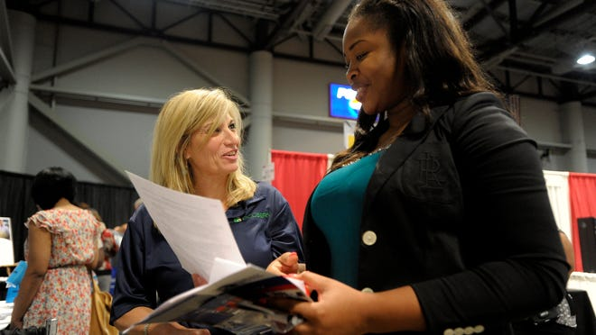 Margaret Greene, a human resources administrator with Ecoserv, speaks to Sope Shopeju, who just received a master's degree in computer science from UL,  during the Lafayette Economic Development Authority Job Fair at the Cajundome Convention Center in Lafayette.  Paul Kieu, The Advertiser