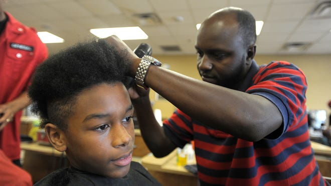 Alex Davis, right, cuts the hair of Tyrek Smith, 13, during the Kuts for Kids event at Blue Cliff College in 2014.