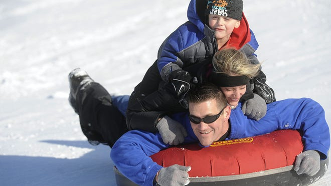 Rob DeSmith steers a tube down the hill at Burchfield Park with his wife Theresa and son Bryson hanging on and having fun in 2012.
